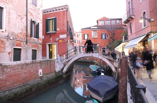 Waterway with old buildings and people on sidewalks in Venice