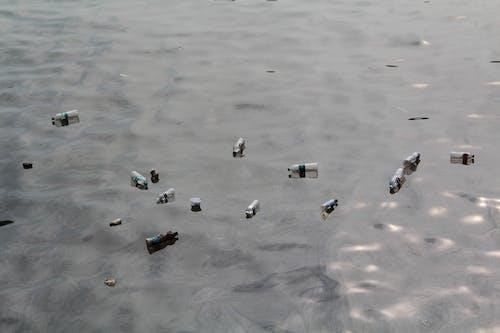 White and Blue Plastic Bottles on White Sand