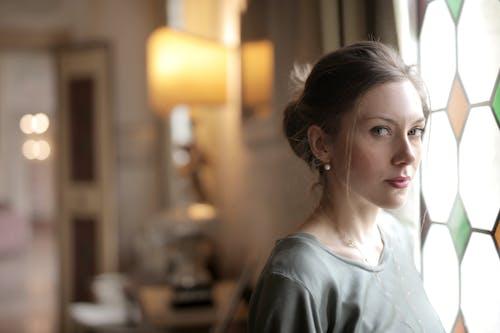 Pensive woman in luxury room near window on sunny day