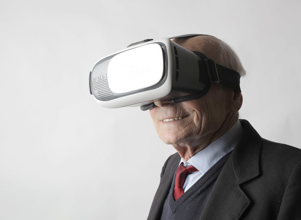 Smiling elderly gentleman wearing classy suit experiencing virtual reality while using modern headset on white background