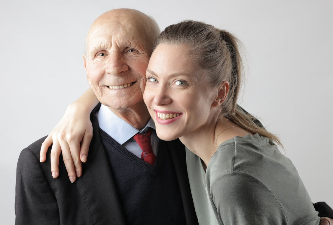 Delighted senior father and adult daughter hugging in studio