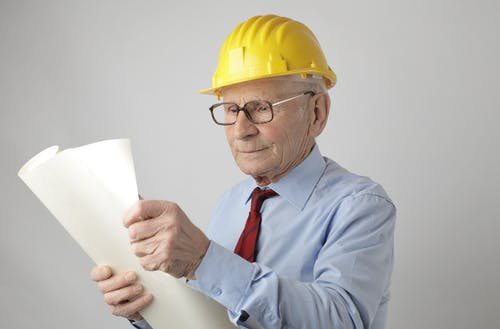 Senior male engineer reading blueprint in studio
