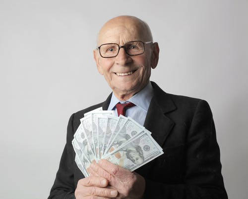 Man In Black Suit Holding Dollar Bills