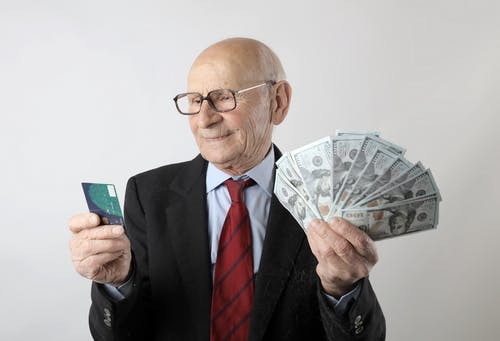 Man In Black Suit Holding Banknotes And Credit Card