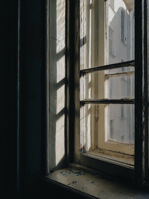 Old shabby wooden window frame in dark room