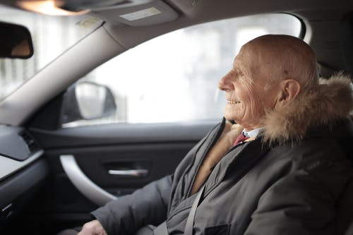 Side view of content elderly male in suit and outerwear sitting in front seat of contemporary automobile and looking away