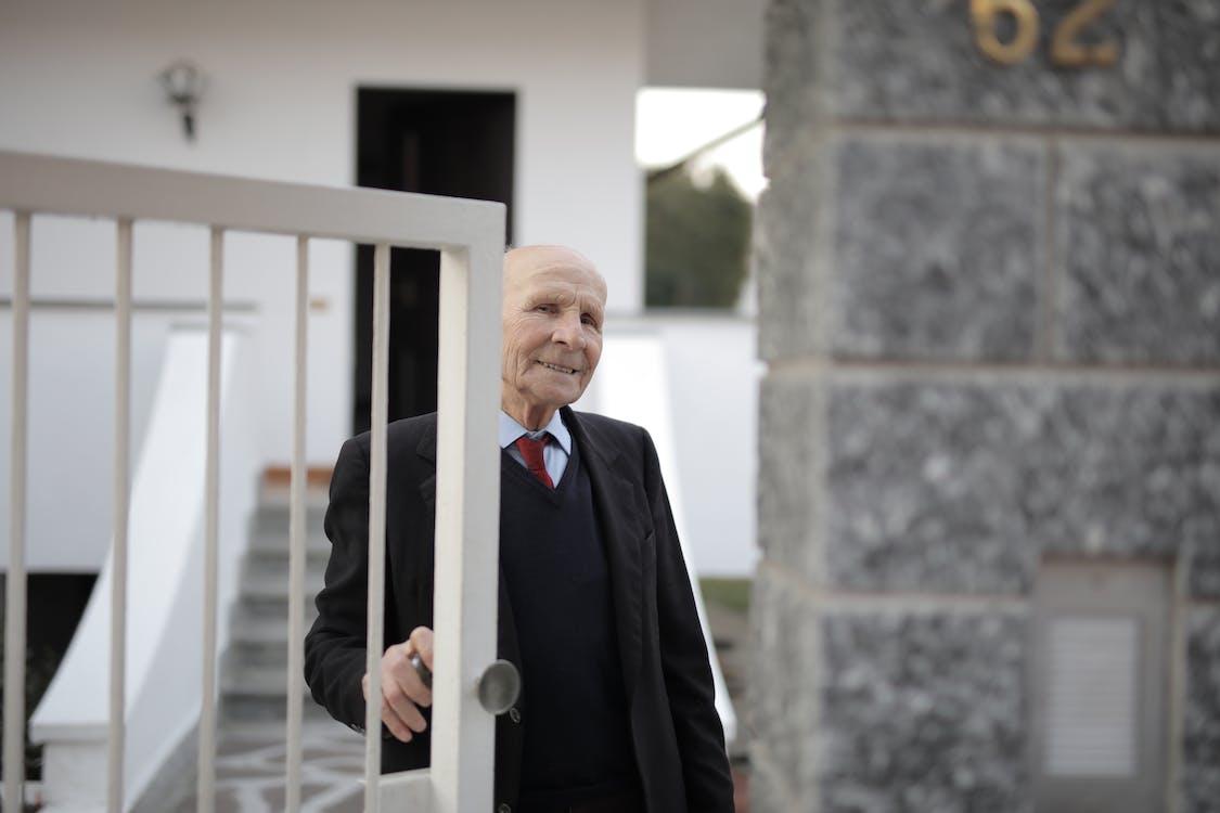 Man in Black Suit Standing Opening The Door