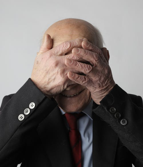 Portrait Photo of Man in Black Suit Jacket Covering His Face with His Hands