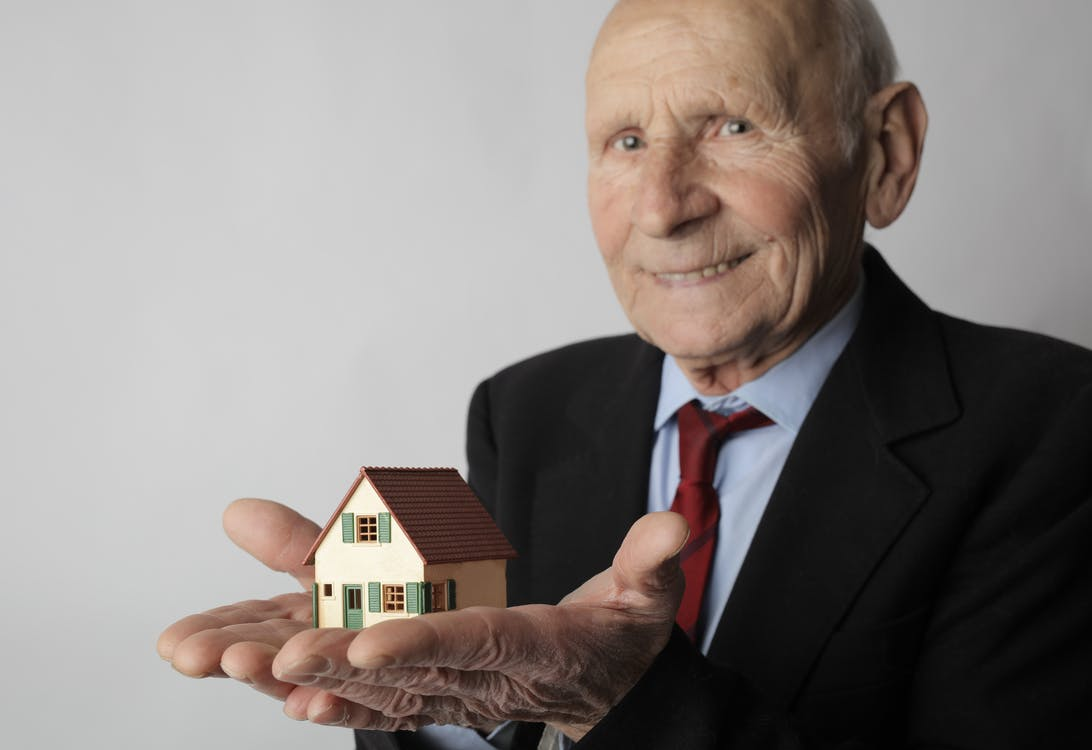 Man in Black Suit Holding Miniature House