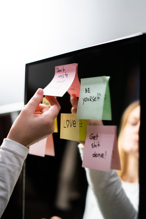 Woman in White Long Sleeve Shirt Holding Sticky Note