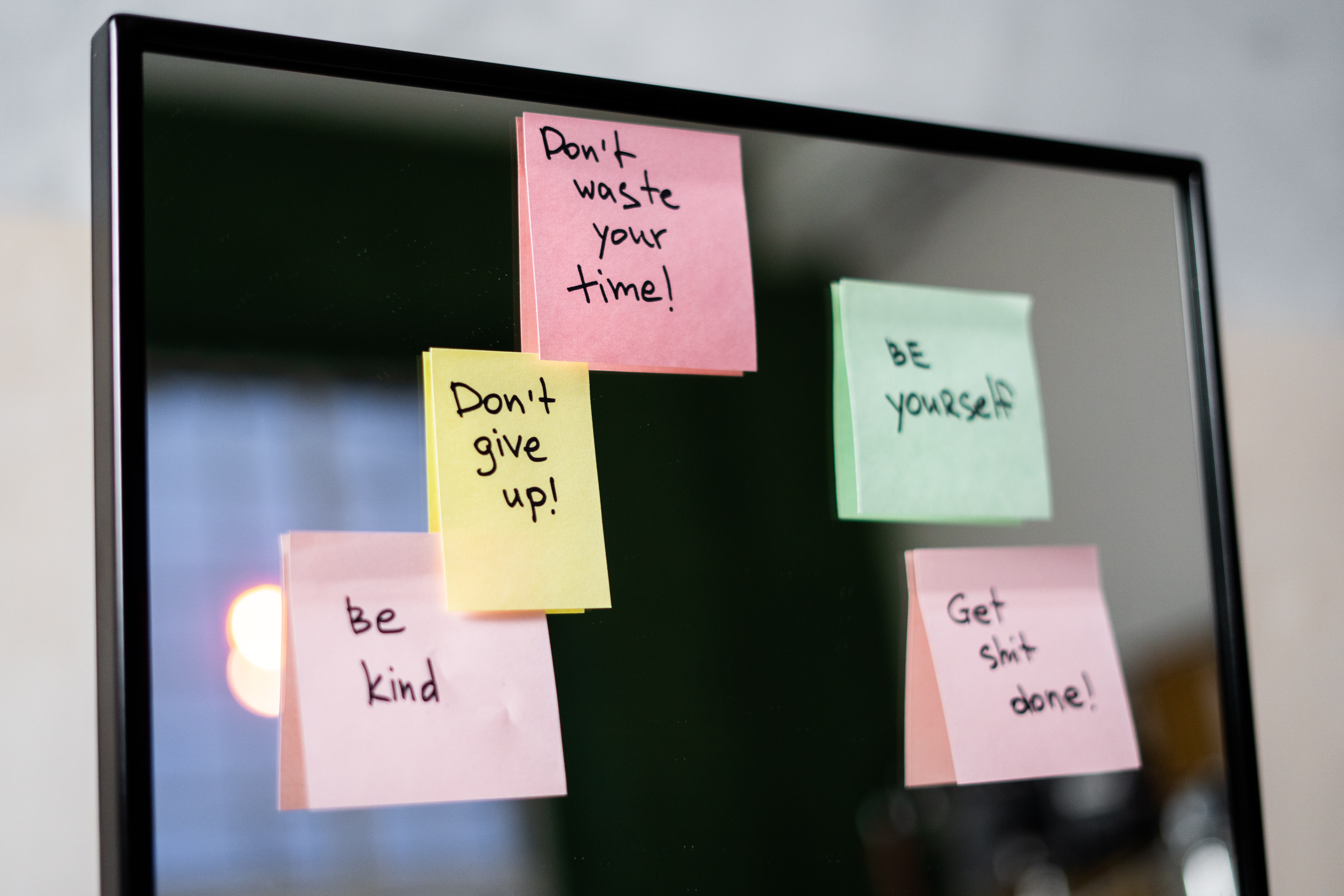 Mirror with post-it notes stuck on it with motivational reminders