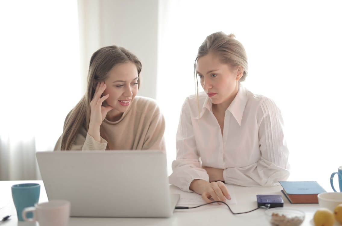 Female workers in casual outfit sitting together at table in bright workplace and thinking of business strategy
