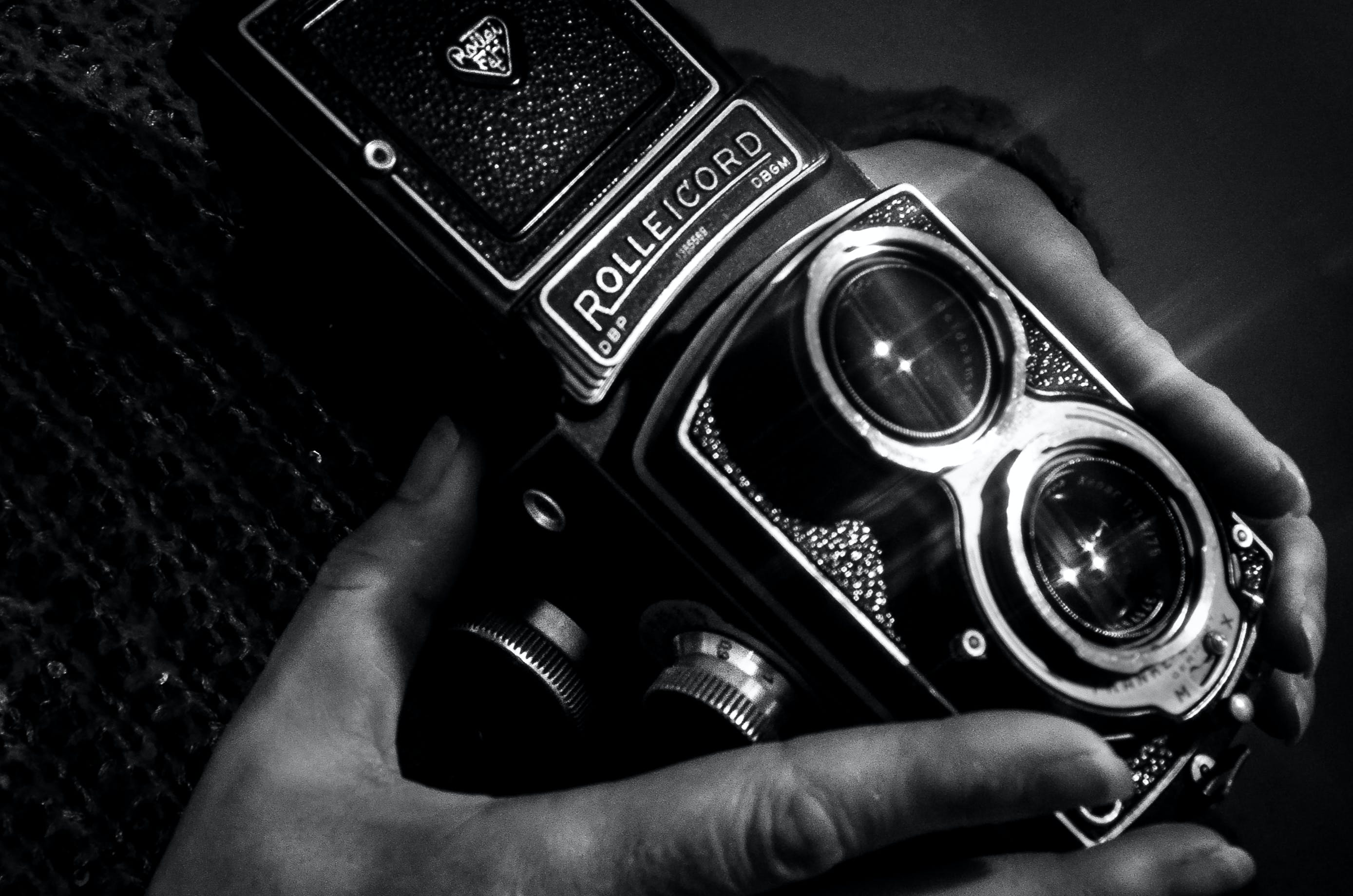 Grayscale Photography of Person Holding Rolleicord Camera