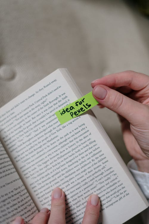 Person Holding A Book And Green Sticky Note