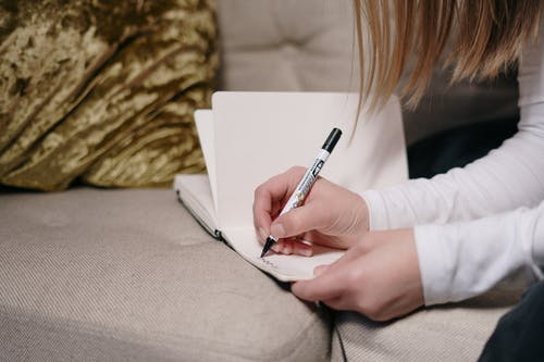 Person In White Long Sleeve Shirt Holding A Pen Writing on White Paper