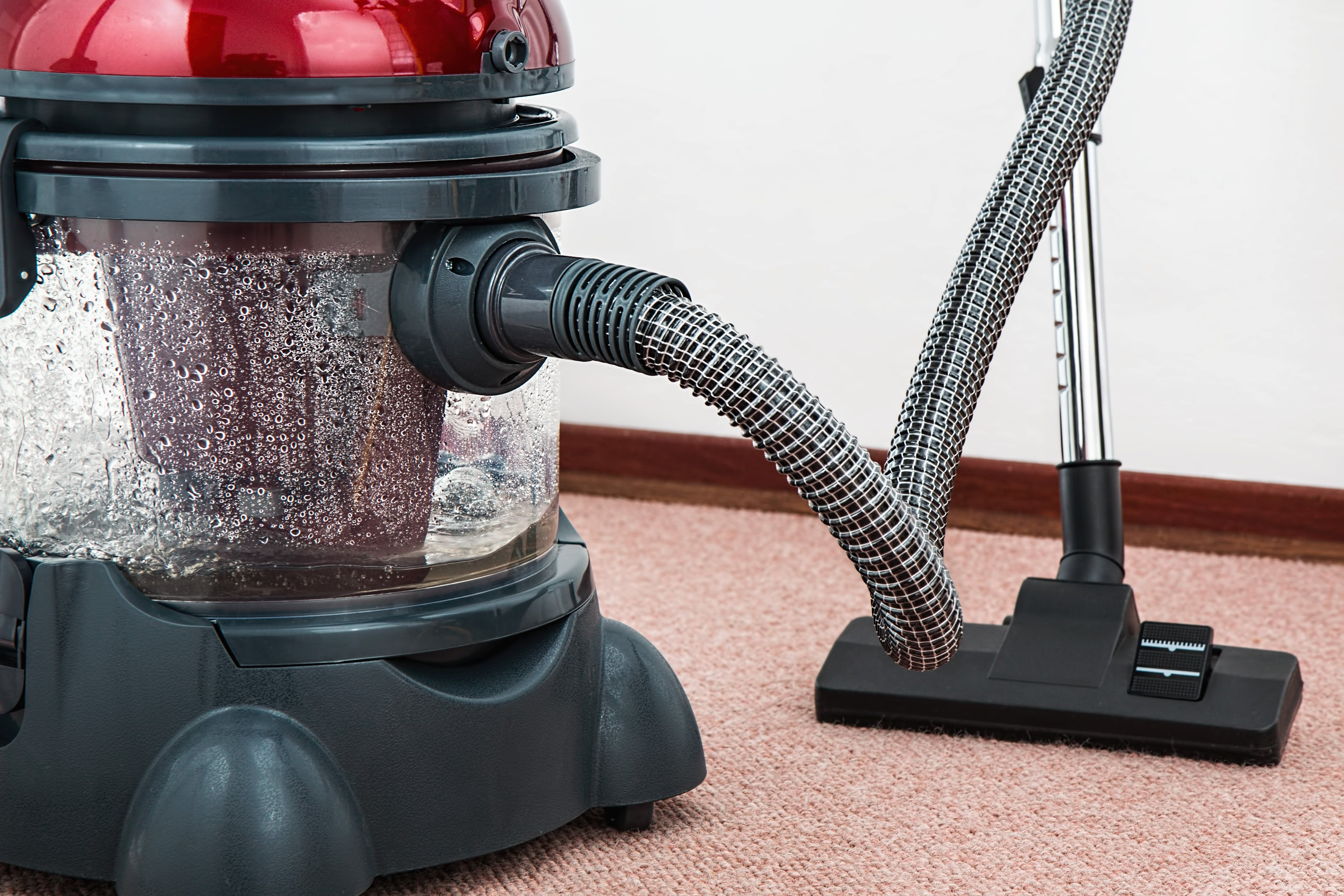 Black and Red Canister Vacuum Cleaner on Floor