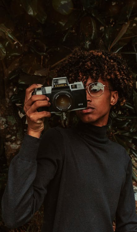 Stylish African American young male millennial in turtleneck and eyeglasses taking picture on vintage photo camera while standing near green tree in park