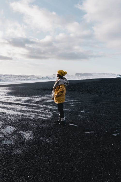 Woman in Yellow Jacket and Yellow Hat Standing on Black Sand