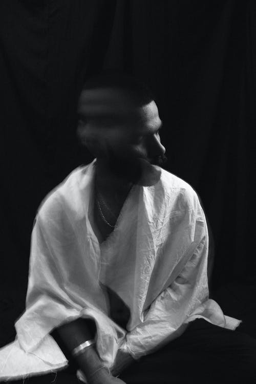 Black and white of lonely melancholic male in white shirt shaking head in motion sitting against black background