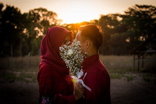Free stock photo of backlight, couple, flower bucket, prewedding