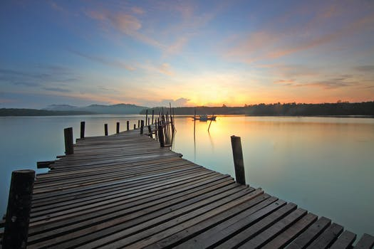 Brown Wooden Dock On Calm Body Of Water Surrounded By