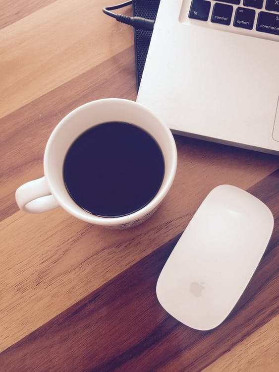 Apple Magic Mouse Beside Cup of Black Coffee