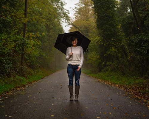 Woman in White Top and Blue Denim Jeans Holding Umbrella Walking on Road