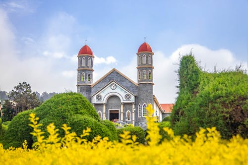 Old Catholic church in well maintained garden against blue sky