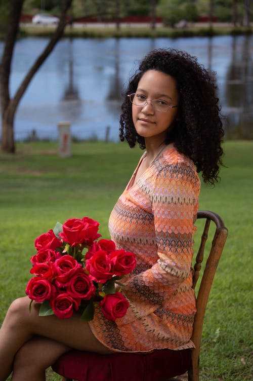 Woman in Orange Dress Wearing Eyeglasses Sitting on Brown Chair Holding Red Roses