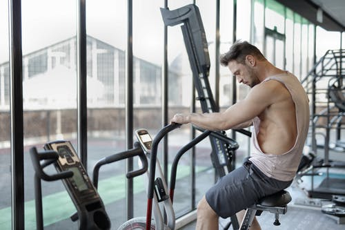 Strong sportsman using exercise bike in gym