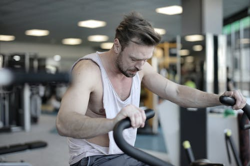 Exhausted male athlete with muscles training on exercise machine and working on endurance in modern sports center