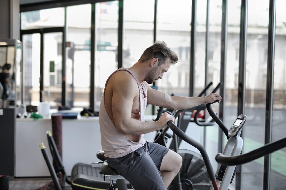 Exhausted athletic man training on exercise bike
