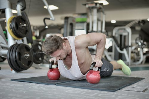 Muscular sportsman doing push ups on kettlebells in gym