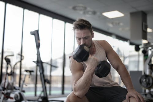 Determined muscular sportsman exercising with dumbbell