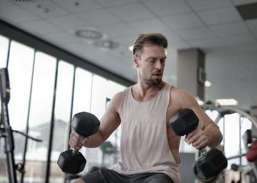 Strong focused sportsman exercising with dumbbells in modern gym