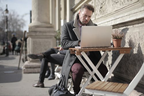Man in Black Jacket Sitting on Brown Wooden Folding Chair Using Macbook