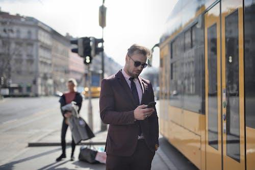 Man in Brown Suit Standing on Sidewalk Using Phone