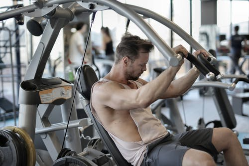 Muscular man exercising with shoulder press machine in gym