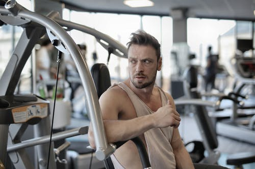 Brutal sportsman resting on exercise machine in gym