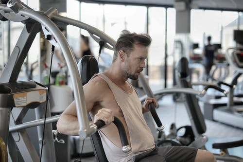 Strong sportsman exercising with shoulder press machine in gym