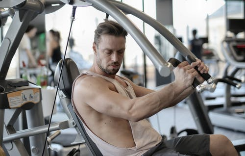 Side view of confident muscular man doing exercises on shoulder press machine while training in modern sports center