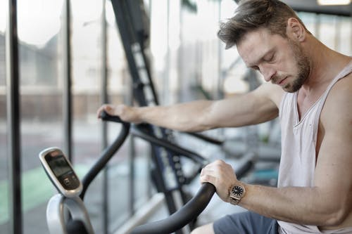 Tired sportsman using exercise bike during training in gym