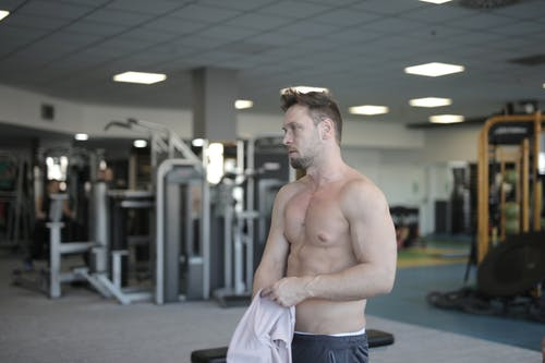 Sweaty shirtless sportsman resting after training in gym