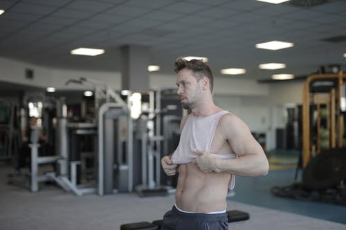 Strong athletic man putting on sportswear in gym