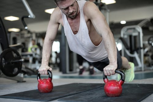 Muscular sportsman pushing up on kettlebells