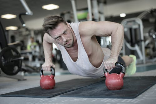 Determined strong sportsman doing push ups in gym