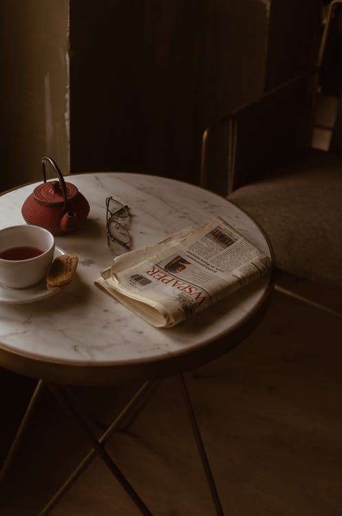 From above of round marble textured table with tea set placed near newspaper and eyeglasses in retro style cafe
