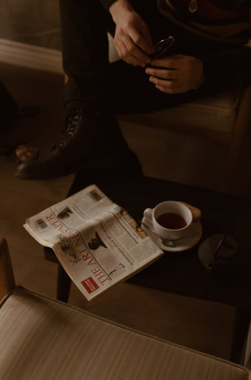 From above of crop anonymous man with eyeglasses in hands sitting on chair near small table with newspaper and tea set during breakfast