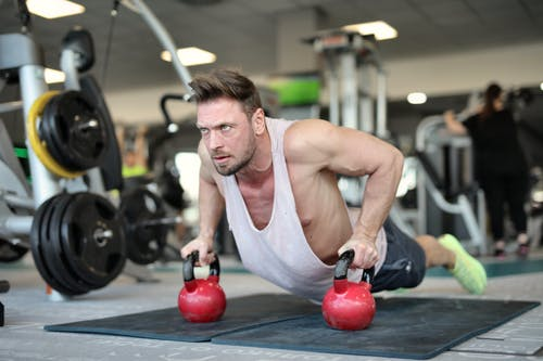 Low angle of strong sportsman making effort and pushing up on metal kettlebells during workout in modern gym and looking away