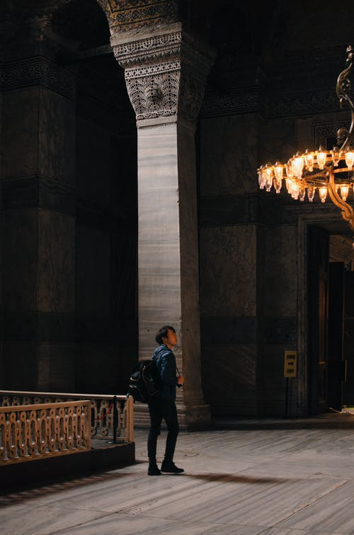 Anonymous young tourist visiting ornamental cathedral